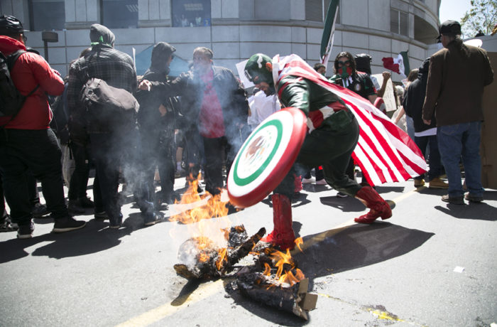Captain Mexico puts out a burning Trump piñata outside the California Republican Convention at the Hyatt Regency in Burlingame on April 29. Photo Gabriella Angotti-Jones