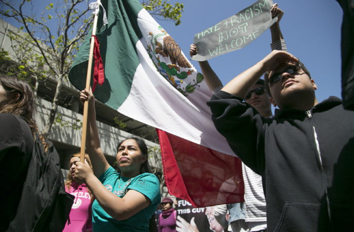 San Mateo resident Silvia Yoc, 19, holds the Mexican flag during a protest outside of the California Republican Convention at the Hyatt Regency in Burlingame on April 29. Photo Gabriella Angotti-Jones.