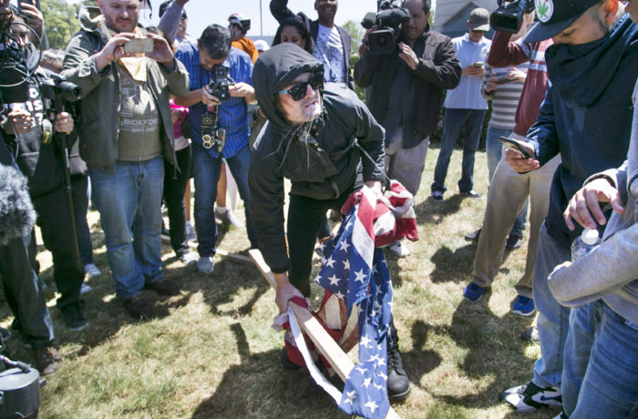 An unaffiliated protester prepares to burn a flag outside the California Republican Convention at the Hyatt Regency in Burlingame on April 29. Photo Gabriella Angotti-Jones