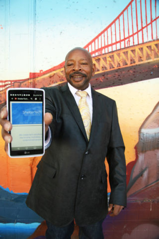 """Darcel Jackson, founder of """"Shelter Tech"""" and """"Ask Darcel,"""" poses with his mobile phone in front of a mural of the Golden Gate Bridge at 24th and Folsom streets on June 26. Photo Adrian Pintor"""