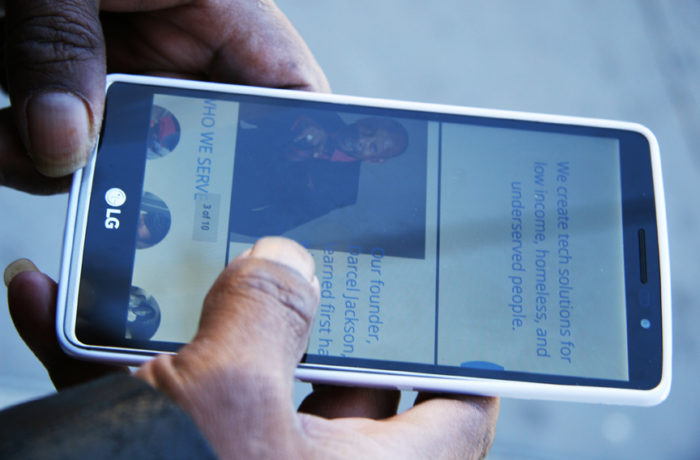 Darcel Jackson holds his mobile phone, which displays a photo of him on the masthead of AskDarcel.org a resourceful website built to help low-income, homeless and underserved people. Photo Adrian Pintor