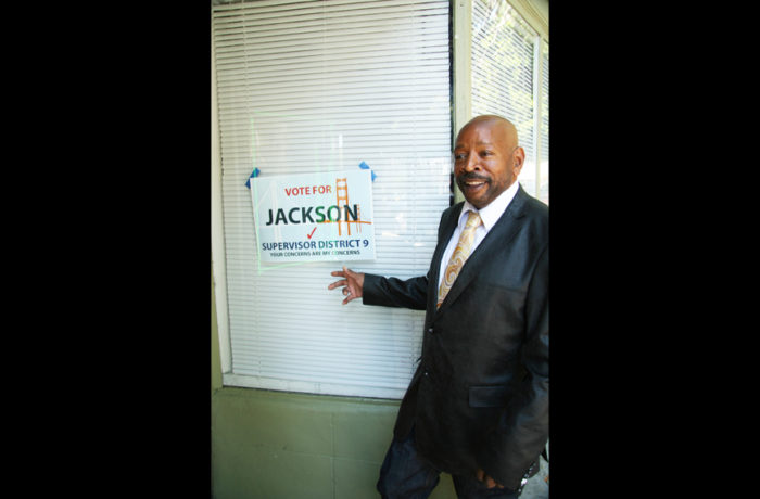 Darcel Jackson poses next to a poster for his campaign as supervisor, at the corner 24th and Lucky streets on June 26. Photo Adrian Pintor