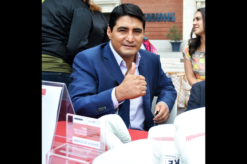 "Erik ""El Terrible"" Morales signs boxing gloves at San Francisco's Yerba Buena Gardens during the recent dedication ceremony for The Mexican Museum. Photo Alejandro Galicia Díaz"