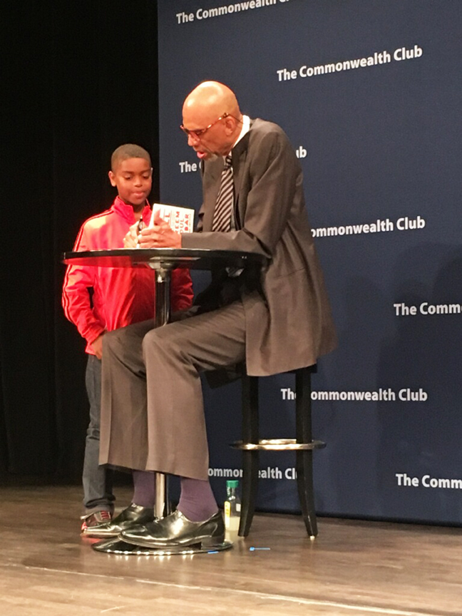 Kareem Abdul-Jabbar (right) signs a copy of his book for a young fan on Aug. 30 in San Francisco. Photo Alejandro Galicia-Díaz