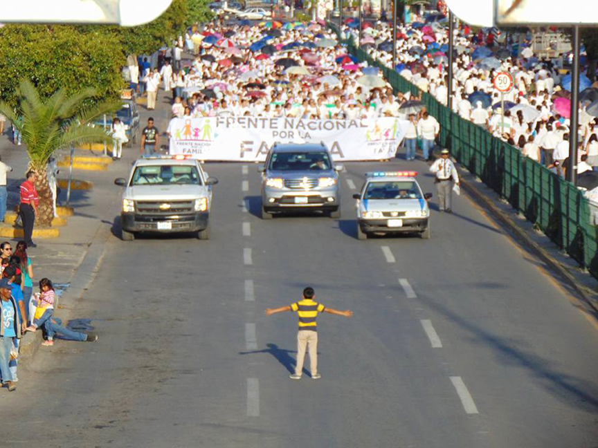A 12-year-old boy stands in front of a contingent of protesters opposing a new proposal of expanded LGBT rights and gender education, in Celaya, Guanajuato. Photo: Manuel Rodriguez