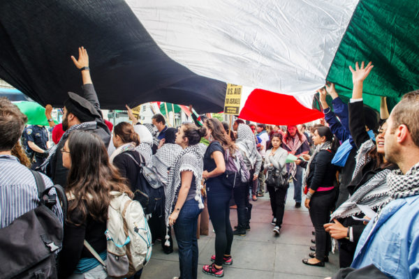 A crowd holds a Palestinian flag in front of the Israeli Consulate in San Francisco on July 7, 2014. Photo: El Tecolote Archives/Ramsey El-Qare