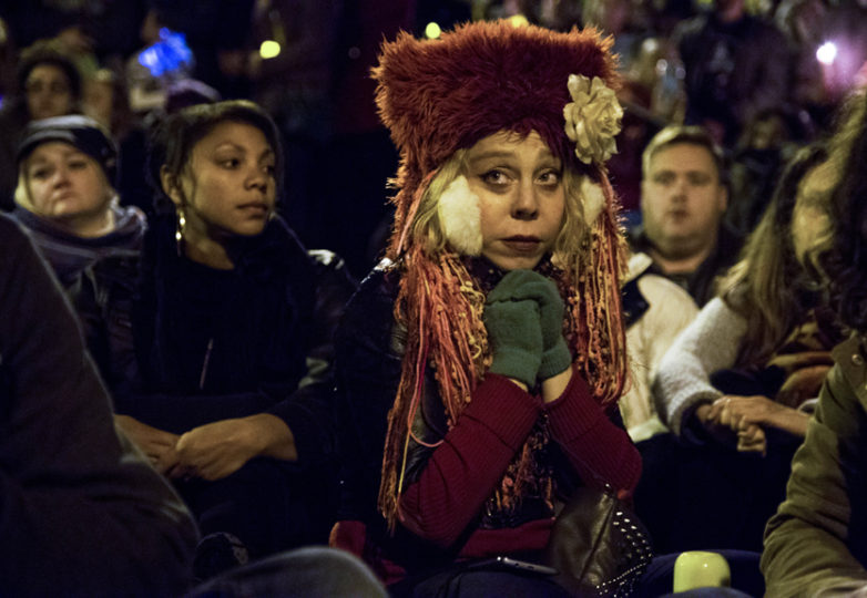 Leslie Landberg, an Oakland resident who has been attending underground rave events for twenty years, sits in the crowd at a vigil honoring the lives of the victims lost in a fire at Ghostship, a warehouse venue for artists in the Fruitvale District. Photo: Natasha Dangond