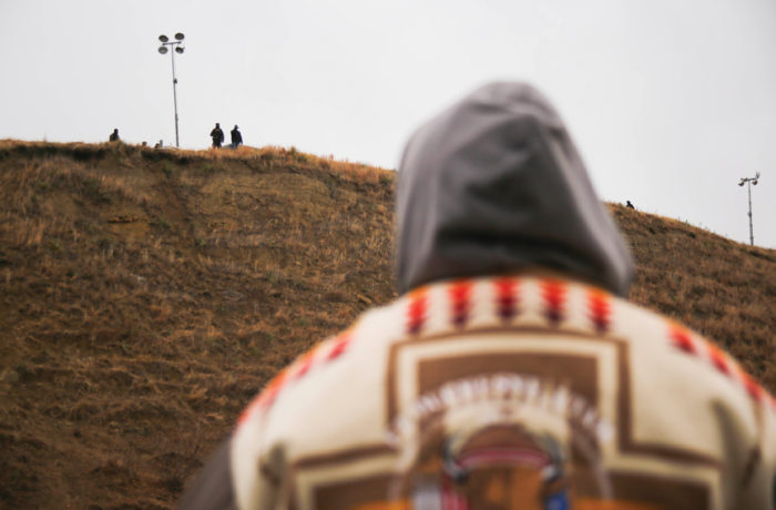 A water protector stares at authorities on top of a hill across the Missouri River near Turtle Island at the Standing Rock Indian Reservation in North Dakota on Nov. 24. Photo Joel Angel Juárez
