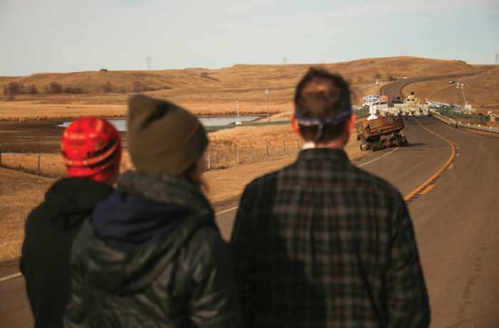 Water protectors stare at a barricade blocking Highway 1806 restricting access to the construction site of the Dakota Access Pipeline at the Standing Rock Indian Reservation in North Dakota on Nov. 25. Photo: Joel Angel Juárez