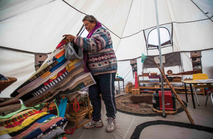 Unci Betty, a trained Montessorian school teacher folds a quilt  Nov. 25 inside a tent she set up for teaching children alternative methods of schooling at Standing Rock Indian Reservation. She is currently working with volunteers to move the school into a bigger teepee to fit more children for her school to continue through the winter. Photo: Natasha Dangond