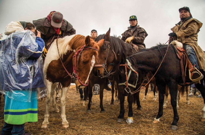 Water protectors from Oceti Sakowin Camp on Standing Rock Indian reservation arrive by horse on Nov. 24 at the foot of Turtle Hill for a direct action against authorities. Photo: Natasha Dangond