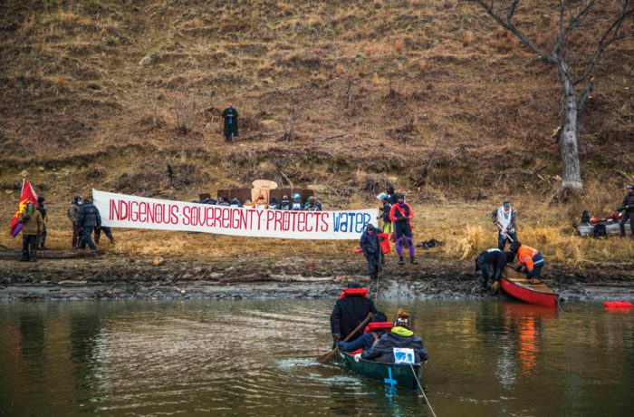 Water protectors cross the river in canoes to gather at the foot of the Cannonball River on Thanksgiving for a direct action against Dakota Access Pipeline, Nov. 24. Photo: Natasha Dangond