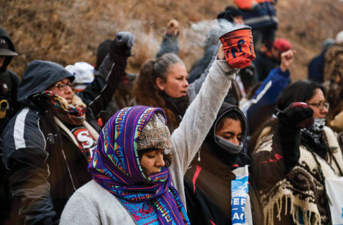 Water protectors at Turtle Hill near Standing Rock Indian Reservation raise their arms during a ceremonial prayer to the four directions on Nov. 24. Photo: Natasha Dangond