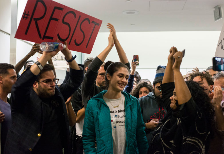 Nilofar Radgoudari (Center, Blue Coat) announces that her father, Menti Radgoudari, has just been released after being detained at San Francisco International Airport (SFO) for five hours on Saturday, January 28. Her father is a green card holder from Iran. Photo: Desiree Rios