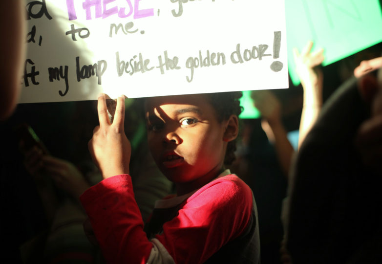 Rode Hartsough, 8, San Francisco resident, carries a pick it sign with the Statue of Liberty  poem during the protest taking place at the arriving terminals at the SFO International Airport in San  Francisco, Calif. on January 28, 2017. Photo: Janett Perez