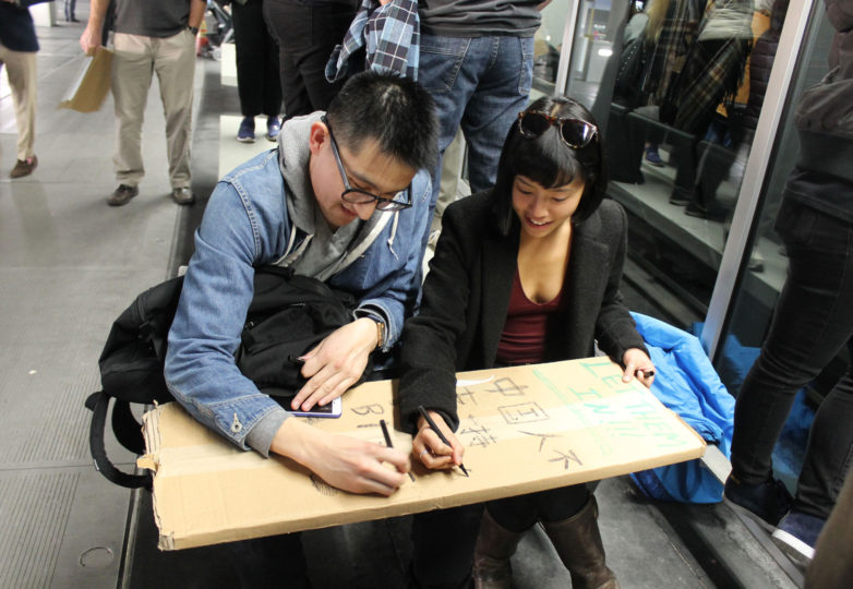 Jack Leng (left), 26, San Francisco resident and Lucinda Ng (right), 27, San Francisco resident  write Chinese characters on a sign to participate in a protest at the SFO International Airport in San  Francisco, Calif. on January 28, 2017. Photo: Janett Perez