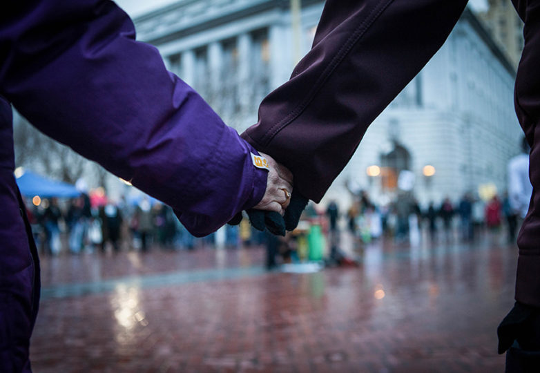 The crowd of Anti-Trump protesters brave the heavy rain and join hands at United Nations Plaza in peaceful protest on inauguration day, Friday, Jan. 20, 2017, San Francisco, Calif. (Photo by Ekevara Kitpowsong)