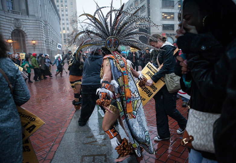 Aztec dancers and Anti-Trump protesters brave the heavy rain and join hands at United Nations Plaza in peaceful protest on inauguration day, Friday, Jan. 20, 2017, San Francisco, Calif. (Photo by Ekevara Kitpowsong)