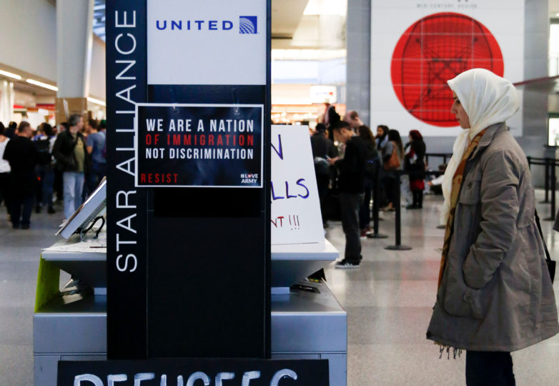 A woman looks at protester's signs at the international terminal of San Francisco International Airport in San Francisco, Calif. Sunday, January 29, 2017 to draw attention to President Donald Trump latest executive order to deny citizens of seven Muslim-majority countries from entering the United States. Photo by Emma Marie Chiang