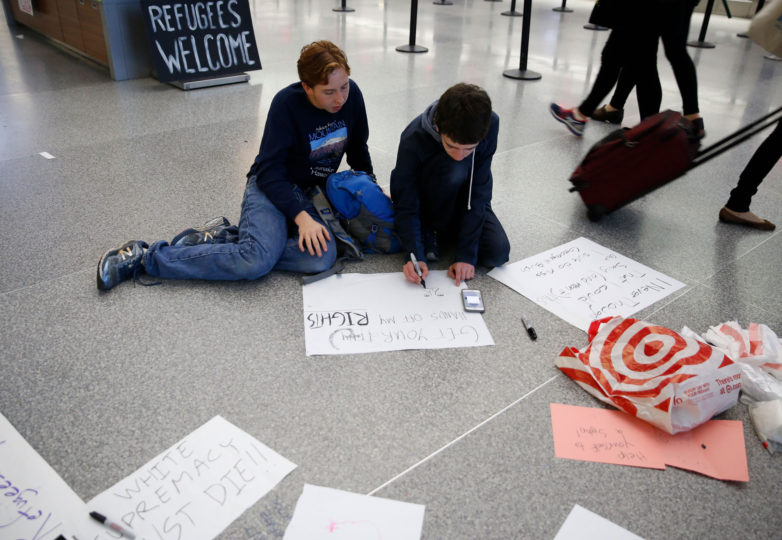 age, 16, (right) and Milo, 16, (left) make a sign during a protest at the  international terminal of San Francisco International Airport in San Francisco, Calif. Sunday, January 29, 2017 to draw attention to President Donald Trump latest executive order to deny citizens of seven Muslim-majority countries from entering the United States. Photo by Emma Marie Chiang