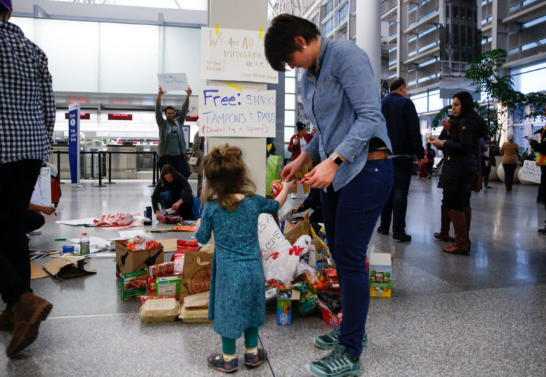 Angela Clements and daughter Hazel, 2, get free snacks during a protest at the international terminal of San Francisco International Airport in San Francisco, Calif. Sunday, January 29, 2017 to draw attention to President Donald Trump latest executive order to deny citizens of seven Muslim-majority countries from entering the United States. Photo by Emma Marie Chiang