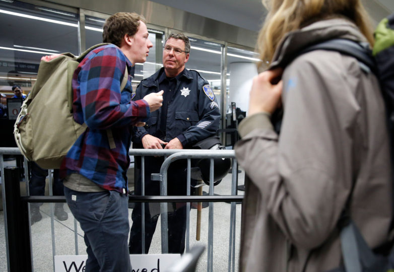 A police officer answers questions to a man trying to go through airline security before he boards his plane at the international terminal of San Francisco International Airport in San Francisco, Calif. Sunday, January 29, 2017. Protesters occupy the international airport to draw attention to President Donald Trump latest executive order to deny citizens of seven Muslim-majority countries from entering the United States. Photo by Emma Marie Chiang