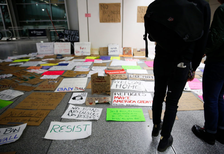 People place their signs near a wall before leaving at the international terminal at San Francisco International Airport in San Francisco, Calif. Sunday, January 29, 2017. Photo by Emma Marie Chiang