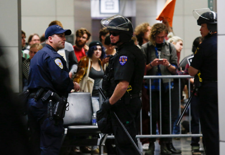 Police officers in riot gear stand guard outside the security checkpoint during a protest held at San Francisco International Airport in San Francisco, Calif. Sunday, January 29, 2017. Photo by Emma Marie Chiang