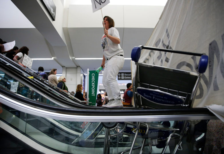 "Constance Hockaday chants while holding a ""No"" sign and stands on a blocked escalator during a protest at the international terminal of San Francisco International Airport in San Francisco, Calif. Sunday, January 29, 2017 to draw attention to President Donald Trump latest executive order to deny citizens of seven Muslim-majority countries from entering the United States. Photo by Emma Marie Chiang"