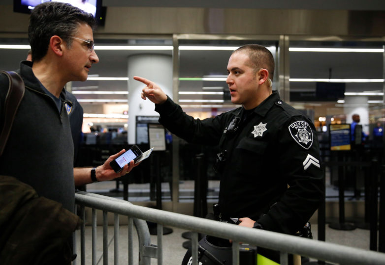 A police officer directs a man trying to go through airline security before he boards his plane at the international terminal of San Francisco International Airport in San Francisco, Calif. Sunday, January 29, 2017. Protesters occupy the international airport to draw attention to President Donald Trump latest executive order to deny citizens of seven Muslim-majority countries from entering the United States. Photo by Emma Marie Chiang