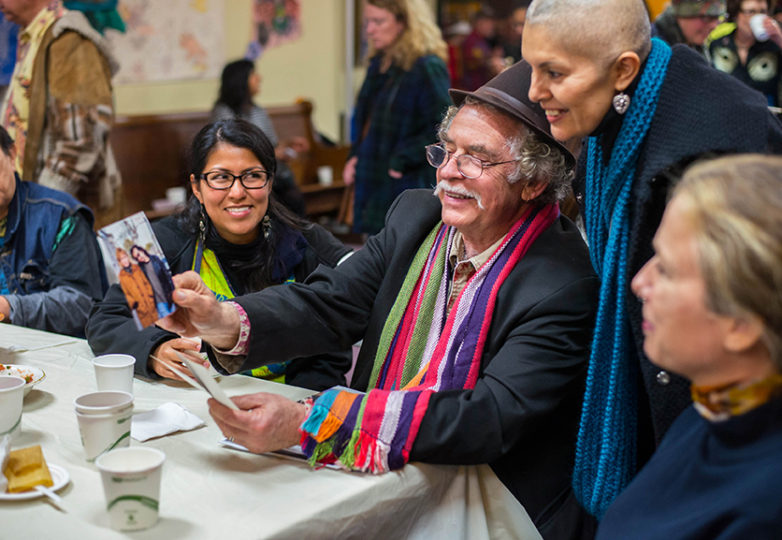 Azuzena Hernandez, Carlos Barón and Mabel Valdivieso look at old photographs of renowned Chicano artist Michael Roman after Roman's memorial service at Saint John Coltrane Church on Friday, Feb. 17. Photo: Desiree Rios