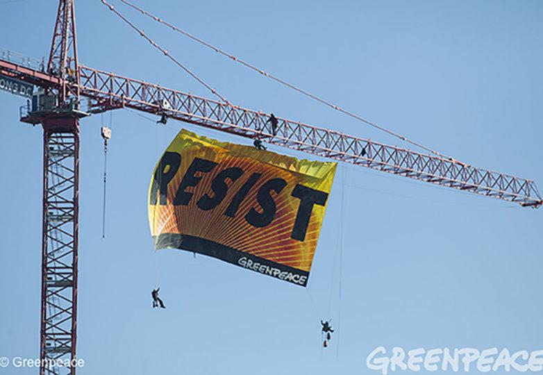 """Siete activistas de Greenpeace montaron en una grúa ubicada a espaldas de la Casa Blanca, y colgaron una manta pintada a mano en la que se podía leer la palabra """"Resiste"""". Courtesía: Greenpeace USA"""