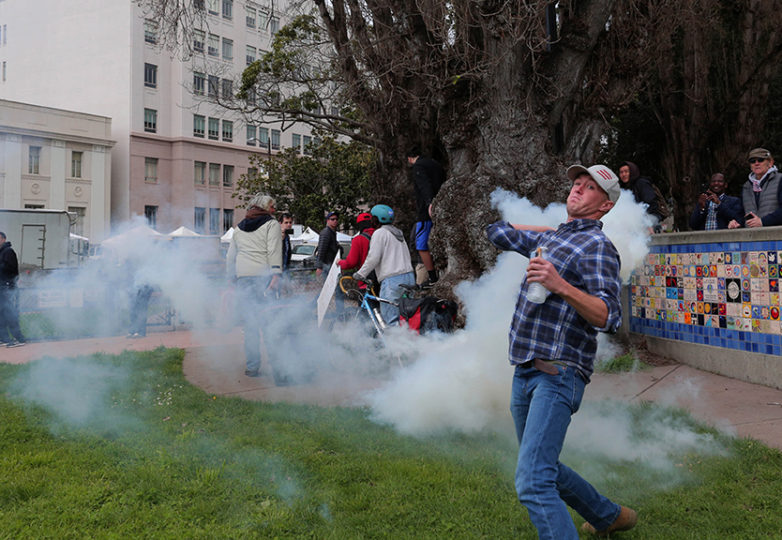 A Trump supporter, who wished to remain unnamed, returns a smoke bomb thrown in his direction during a Pro-Trump rally at Martin Luther King Jr. Civic Center Park  on Saturday, March 4, 2017 in Berkeley, Calif. Numerous clashes between supporters and protesters occurred throughout the afternoon. Photo: Gabriella Angotti-Jones