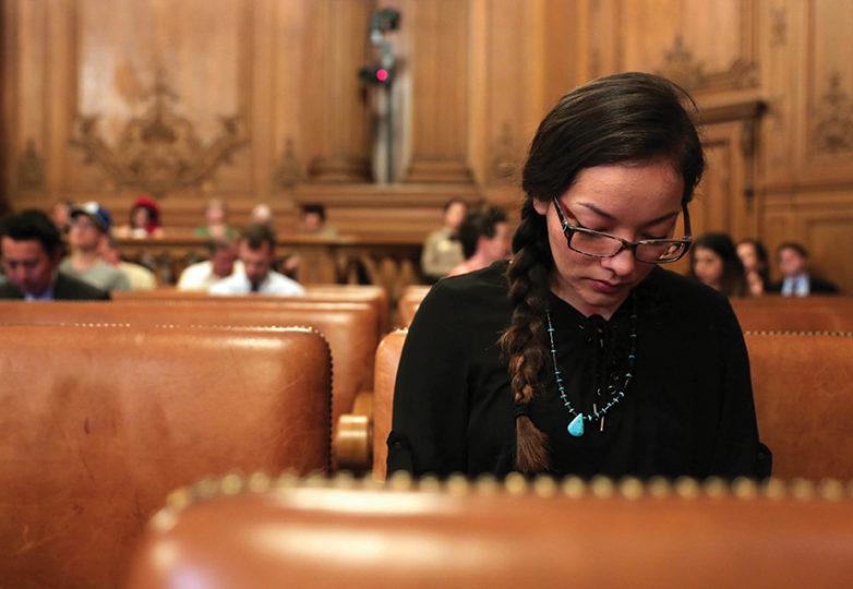 Isabella Zizi, lee sus notas antes de dar su comentario publico. La Junta de Supervisores de San Francisco, aprobó de forma unánime una resolución que instaría al Tesorero a poner una pantalla sobre DAPL con la revisión mensual de inversiones de San Francisco. Foto: Gabriella Angotti-Jones
