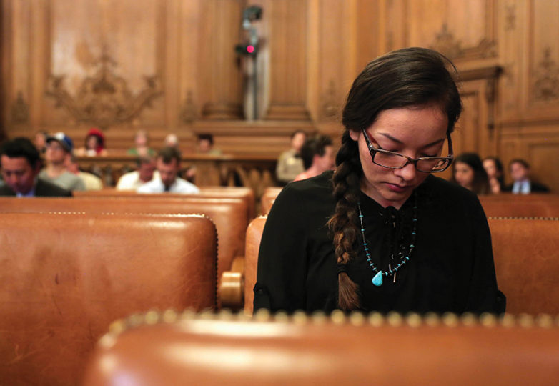 Isabella Zizi, a Northern Cheyenne Arikara Muskogee Creek Native American, reads her notes before making a public comment on Tuesday, March 14, 2017 in San Francisco, Calif. The San Francisco Board of Supervisors unanimously passed a resolution that would urge the Treasurer to put a DAPL screen in San Francisco's monthly investment review.  Zizi has family in North Dakota that will be affected by the pipeline. Photo: Gabriella Angotti-Jones