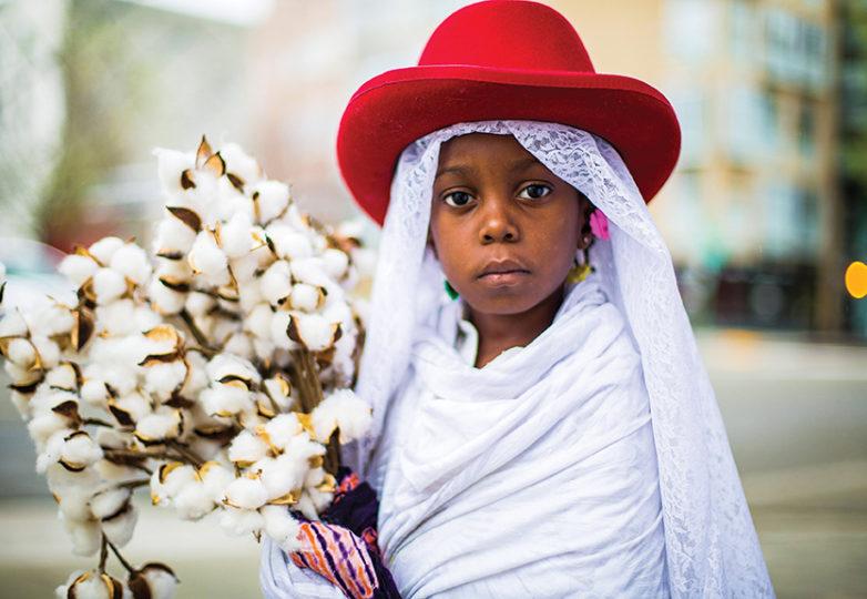 """""""Su nombre es Sa'nya. Su velo es la protección contra de entidades malignas. El sombrero rojo simboliza al guerrero Dios Shango en la religión yoruba, el dios del relámpago, el fuego llamativo para el cambio. El algodón es un símbolo de sus antepasados y un humilde recordatorio del trabajo que la comunidad de color tiene que hacer para superarse. Creo que la mujer es esencialmente una deidad"""". — Karen Seneferu (Grandmother)"""