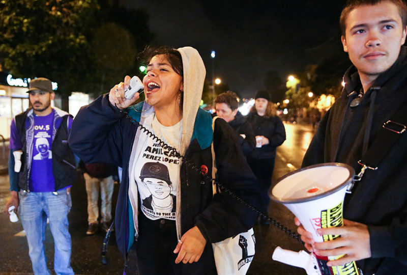 Angela Rey leads a small group of protesters in a chant at 17th and Valencia streets in front of the Mission Police Station on April 12, at a demonstration in response to the District Attorney's office statement to not indict the officers involved in the fatal 2015 shooting of Amilcar Perez-Lopez. Photo: Emma Marie Chiang