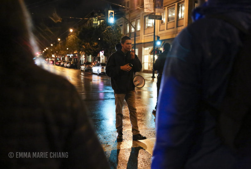 Michael Picasso leads a small group of demonstrators in a chant while blocking off 17th and Valencia streets in front of the Mission Police Station. Photo: Emma Marie Chiang