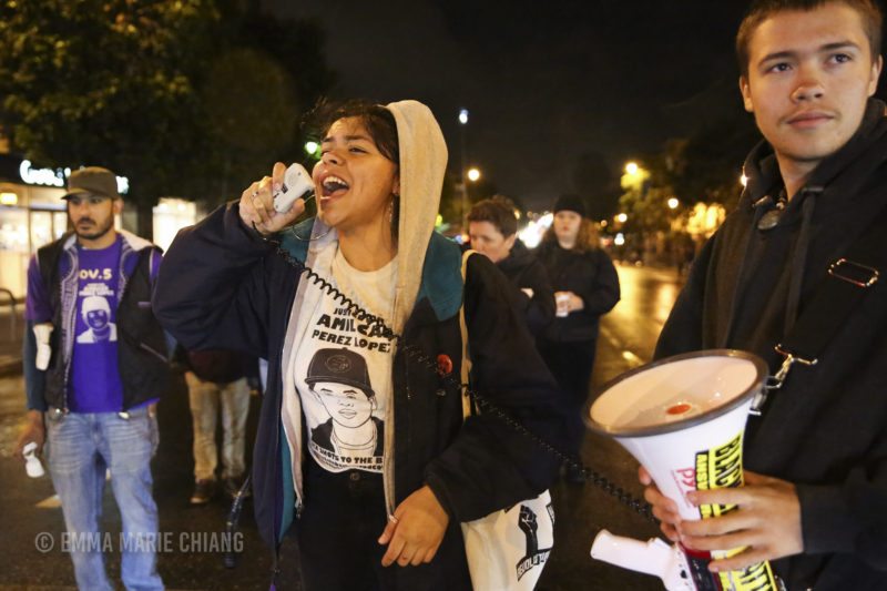 Angela Rey leads demonstrators in a chant while blocking off 17th and Valencia streets in front of the Mission Police Station. Photo: Emma Marie Chiang