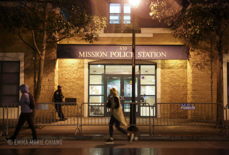 A police officer stands in front of the Mission Police Station blocked off by guard rails as a small group of protesters rally outside. Photo: Emma Marie Chiang
