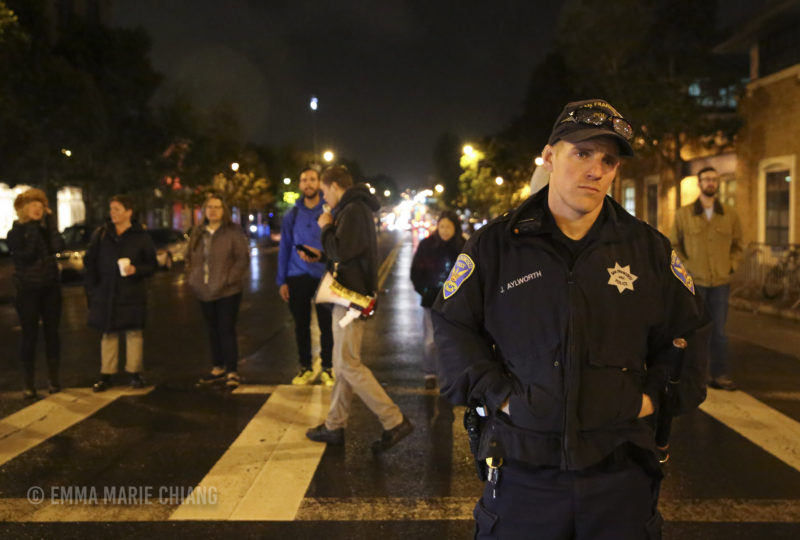 Officer J. Aylworth stands in front of a group of protesters blocking off 17th and Valencia streets in front of the Mission Police Station. Photo: Emma Marie Chiang