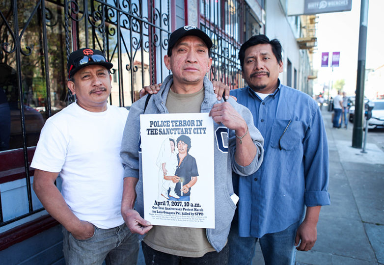 "The family of Luis Góngora Pat, who was fatally shot by SFPD on April 7, 2016. (L-R) Luis Góngora Pat's cousin Luis Poot, his brother José Góngora Pat and his cousin Carlos Poot stand on 17th Street while holding a poster of the ""Police Terror in The Sanctuary City"" march on April 1, 2017. The march is scheduled for Friday, April 7, on the one-year anniversary of the death of Luis Góngora Pat. Photo: Ekevara Kitpowsong"