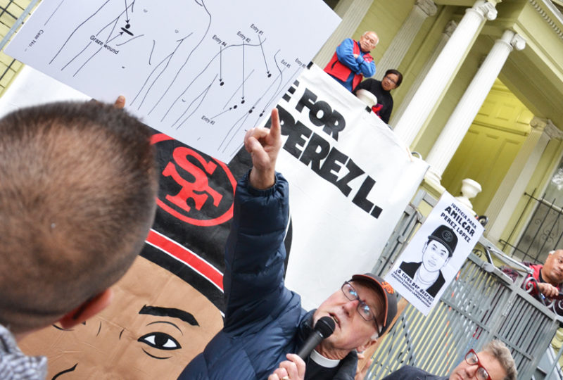 Father Richard Smith points at a diagram from Amilcar Pérez-López's autopsy, outside the home where Amilcar lived at the time of his death, during a vigil on Friday April 24, 2015. Photo Mabel Jiménez