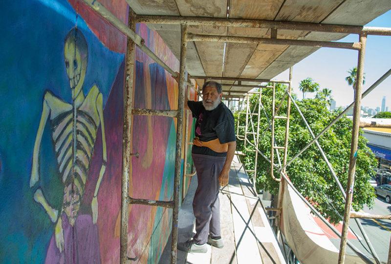 El muralista Carlos Loarca, de 80 años, camina por el andamio que están utilizando para la restauración del mural que decora el exterior del Centro Cultural para las Artes Latinas (MCCLA) el 2 de mayo de 2017. Loarca es uno de los artistas que originalmente participó en la creación del mural y quien está dirigiendo la actual restauración, ayudado por otros muralistas de la comunidad. Foto: Mabel Jiménez