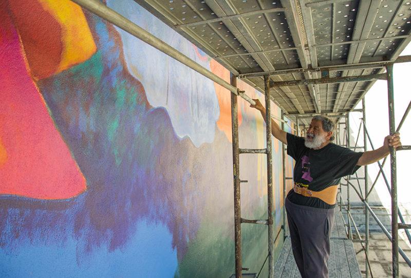 El muralista Carlos Loarca, de 80 años, camina por el andamio que están utilizando para la restauración del mural que decora el exterior del Centro Cultural para las Artes Latinas (MCCLA) el 2 de mayo de 2017. Foto: Mabel Jiménez