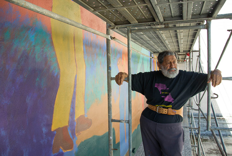 Muralist Carlos Loarca, 80, on the scaffolding being used in the restoration of the mural outside of the Mission Cultural Center for Latino Arts (MCCLA) on May 2, 2017. Photo: Mabel Jiménez