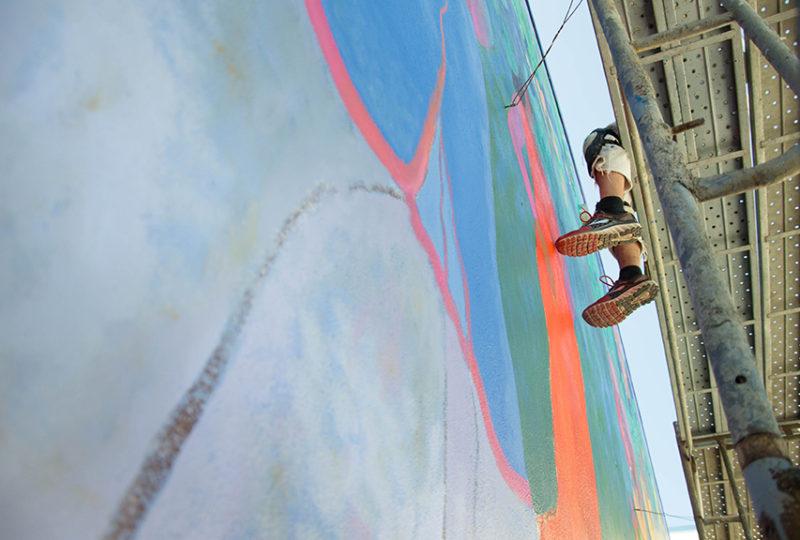 Un muralista trabaja en la restauración del mural afuera del MCCLA. Foto: Mabel Jiménez