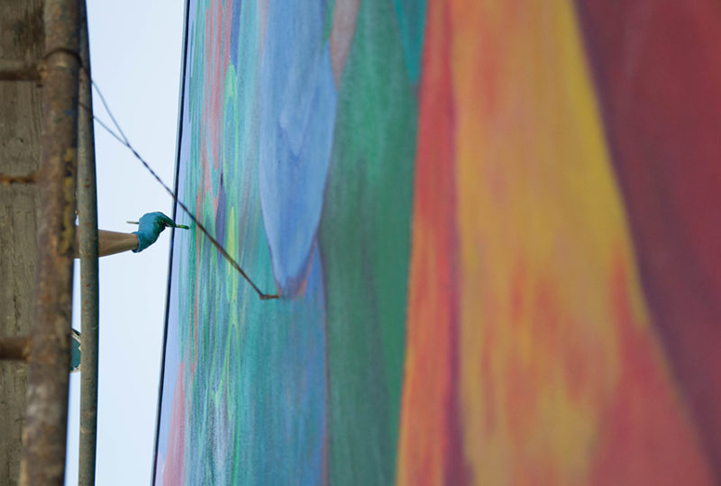 Betsie Miller-Kusz trabaja en la restauración del mural del MCCLA, el 2 de mayo de 2017. Ella es una de las artistas originales que colaboró en la creación del mural. Foto: Mabel Jiménez