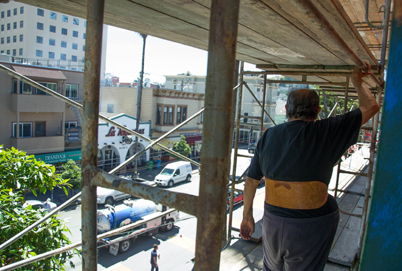 Muralist Carlos Loarca, 80, walks on the scaffolding being used in the restoration of the mural outside of the Mission Cultural Center for Latino Arts (MCCLA) on May 2, 2017. Photo: Mabel Jiménez