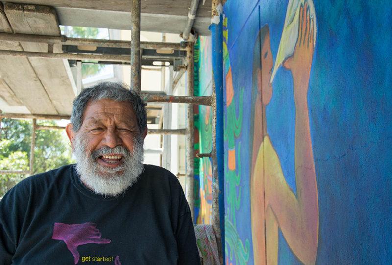 El muralista Carlos Loarca posa para una fotografía en el andamio donde se encuentra trabajando en la restauración del mural fuera del Mission Cultural Center el martes 2 de mayo, 2017. Foto: Mabel Jiménez